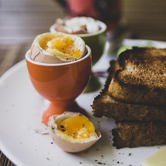 Eitje in een eierdop met toast op een bord